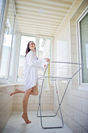 Attractive woman wearing underwear and shirt hanging laundry on the balcony. Stock Photo