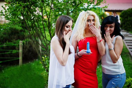 Beautiful bride in red dress showing a soap in penis shape to her bridesmaids at bachelorette party. Stock Photo