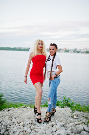 Awesome bride in red dress posing with her bridesmaid on the lakeside.