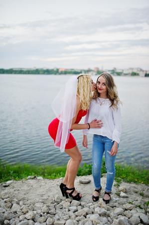 Ehrfürchtige Braut im roten Kleid, das mit ihrer Brautjungfer auf dem See aufwirft.