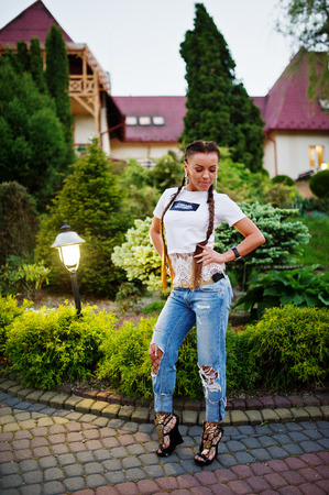 Fabulous bridesmaid wearing jeans and white t-shirt posing outside at bachelorette party.