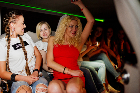 Gorgeous girls having fun while sitting inside the luxurious limousin at bachelorette party. Stock Photo