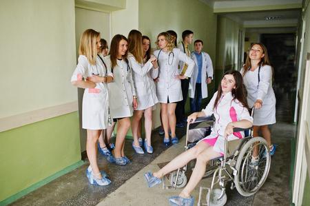 Gekke jonge artsen hebben plezier door zich op een rolstoel in de gang van het ziekenhuis te stellen.