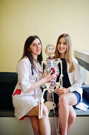 Young doctors having fun by posing with skeleton.