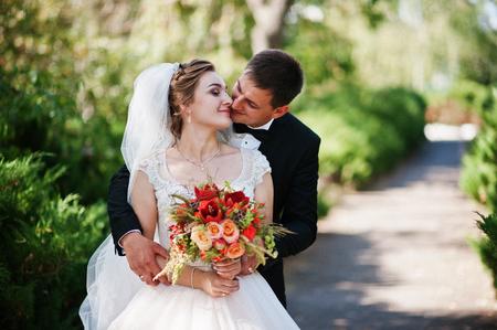 Fantastische bruiloftspaar genieten van elkaars bedrijf in het park.