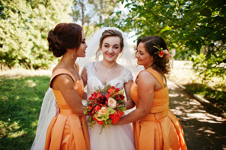 Happy bride having fun with her cool fun bridesmaids in the park on a wedding day. Stock Photo