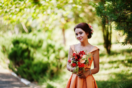 Attractive bridesmaid in orange dress posing with bridal bouquet on a wedding day.