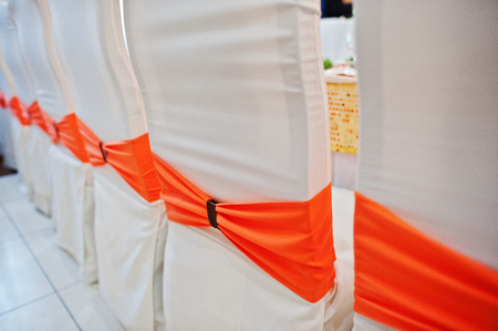 Decorated chairs with orange ribbon for wedding banquet.