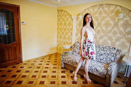 364e8b93e102 Portrait of a gorgeous young woman in floral dress walking in a luxurious  room.