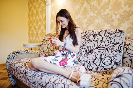 Portrait of a beautiful girl in dress sitting on the couch and texting someone. Stock Photo
