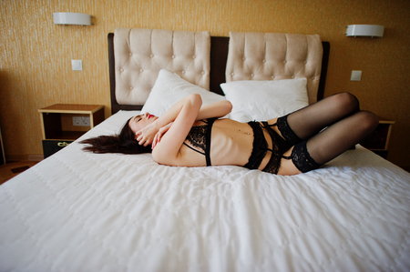Hot young woman laying on a bed and posing in lingerie.