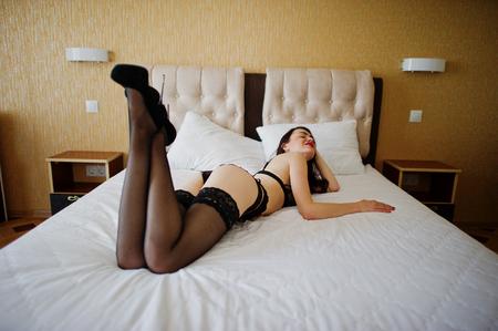 Hete jonge vrouw die op een bed legt en in lingerie en hoge hielen stelt. Stockfoto