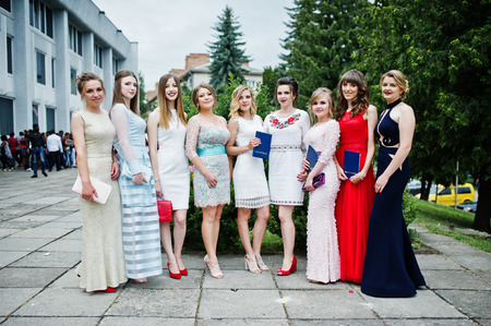 Faulous young women graduates in chic evening gowns posing outside in the park.