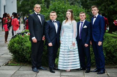 Beautiful girl in evening gown standing along with men in tuxedos on the graduation day. Stock Photo