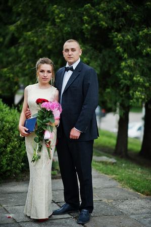 Good-looking couple celebrating their graduation from the university, posing outside in beautiful clothing with flowers.