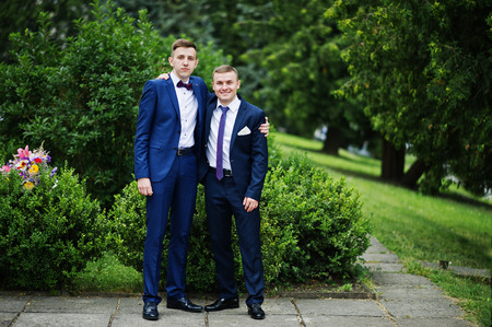 Two intelligent and handsome graduates in tuxedos posing on th graduation day. Stock Photo