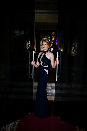 Portrait of a gorgeous young woman in luxurious dress opening the door.