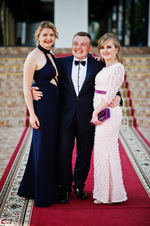 Young man in tuxedo posing with two girls in evening gowns on the graduation ceremony.