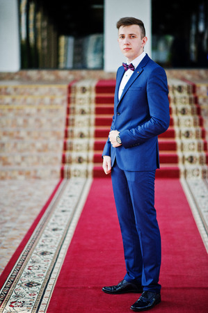 Portrait of an intelligent and handsome young man dressed in tuxedo posing on the red carpet. Stock Photo