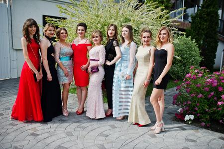 Wdzięczne młode kobiety absolwentki w eleganckich wieczorowych sukniach pozują na zewnątrz w parku.