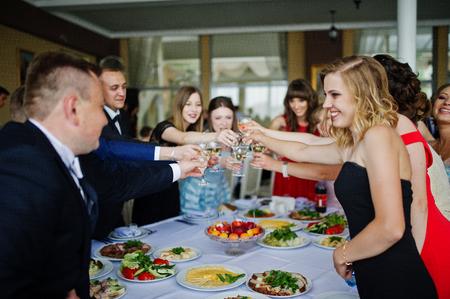 clinking 및 레스토랑에서 대학에서 공부의 끝을 축 하하는 졸업생의 그룹입니다.