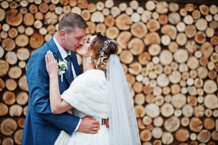 Perfect newly married couple posing on the wooden background.