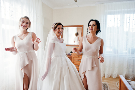 Fabulous young bride posing with her bridesmiads in her room on the wedding day.