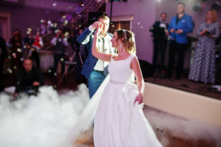 Newly married couple dancing on their wedding party with heavy smoke and multicolored lights on the background. Stock Photo