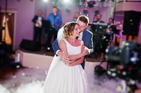 Recentemente coppia sposata ballare la loro festa nuziale con fumo pesante e luci multicolori sullo sfondo. Archivio Fotografico - 83424125