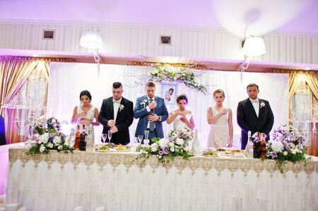 Wedding Couple And Groomsmen With Bridesmaids Praying Before The Meal