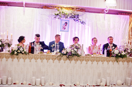 Beautiful wedding couple sitting at their table with bridesmaids and groomsmen sitting beside them.