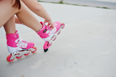 Young woman putting on rollerblades outdoor. Stock Photo