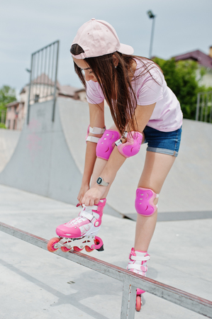 Portrait of a beautiful girl wearing cap, t-shirt and shorts putting on rollerblades outdoor next to the lake.