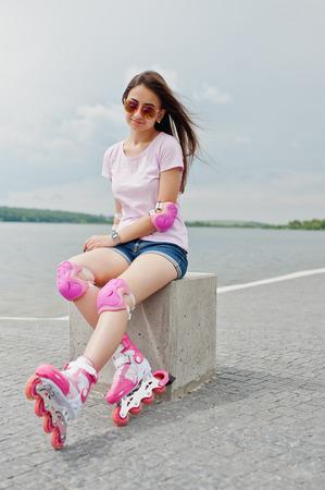 Retrato de una mujer joven atractiva en pantalones cortos, camiseta, gafas de sol y patines sentado en el banco de hormigón en la pista de patinaje al aire libre.