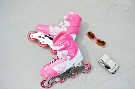Close-up photo of pink rollerblades laying along with an antique camera, sunglasses and a pink cap. Stock Photo