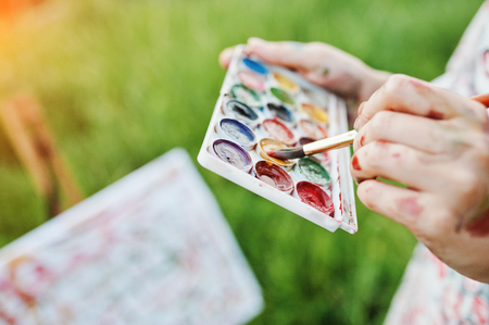 Close-up photo of female hands holding watercolor paints and a brush while painting in nature.