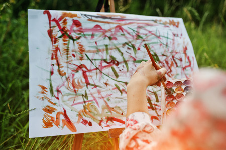 Close-up photo of female hand painting on the paper with watercolors.