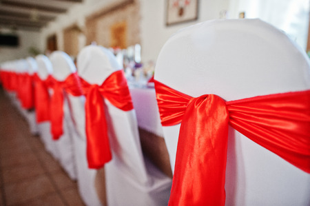 Gorgeously decorated chairs with red bows tied on them