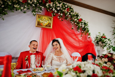 Gorgeous wedding couple sitiing at the table and laughing on theirr wedding day. Stock Photo
