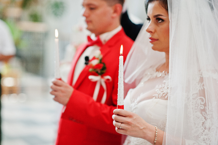 Close-up photo of bride and groom holding candles in the church during wedding ceremony.