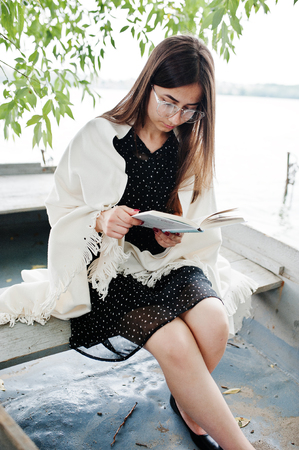 Portrait of an attractive woman wearing black polka dots dress, white shawl and glasses reading a book in a boat on a lake. Stock Photo
