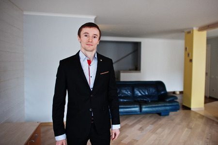 affable: Portrait of a handsome groom posing in his wedding suit in his big apartment.