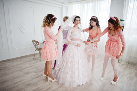 Helpful bridesmaids and mother helping bride to tie the dress up in big light room.a