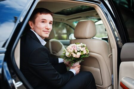 Portrait of a handsome groom sitting in the wedding car with a bouquet in his hands.