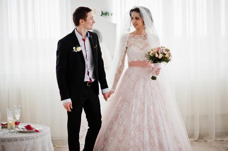 Geweldig bruidspaar genietend van elkaars gezelschap in enorme witte kamer.