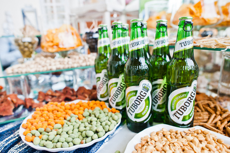 brewery: Hai, Ukraine - August 10, 2017: close-up photo of Tuborg beer on the table next to different snacks.