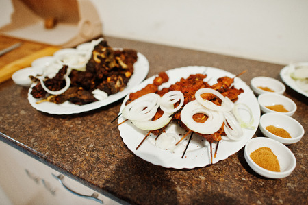 Close-up photo of meals made from meat decorated with onion laying on the surface with spices next to them.