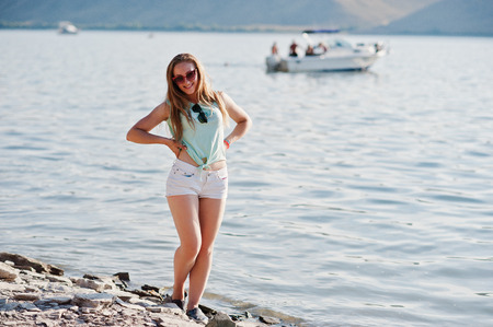 Portrait of a smiling girl standing on the lake shore with a yacht in the background.