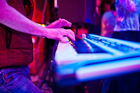 Close-up photo of musicians hands playing the synthesizer in the nightclub.