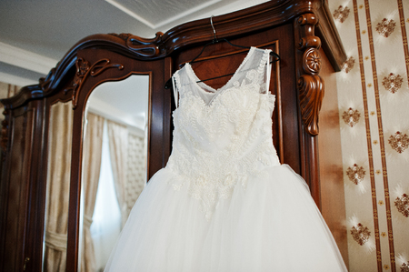Wedding dress hanging on the rack on the wardrobe in the room. Stock Photo